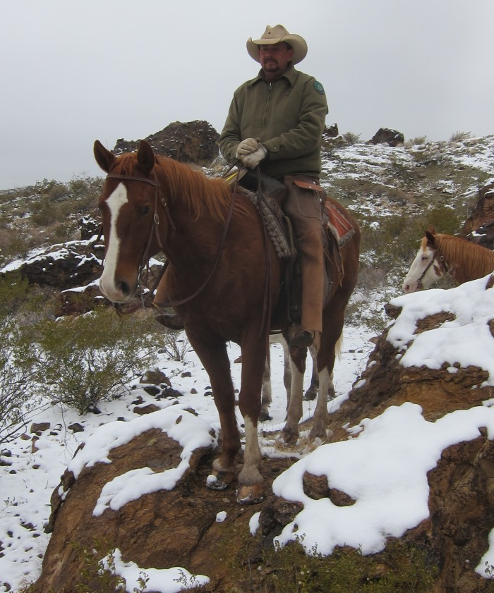 Raul, long time experienced state park hand and guide, shows off his horse's ability by stepping him up on a large rock.