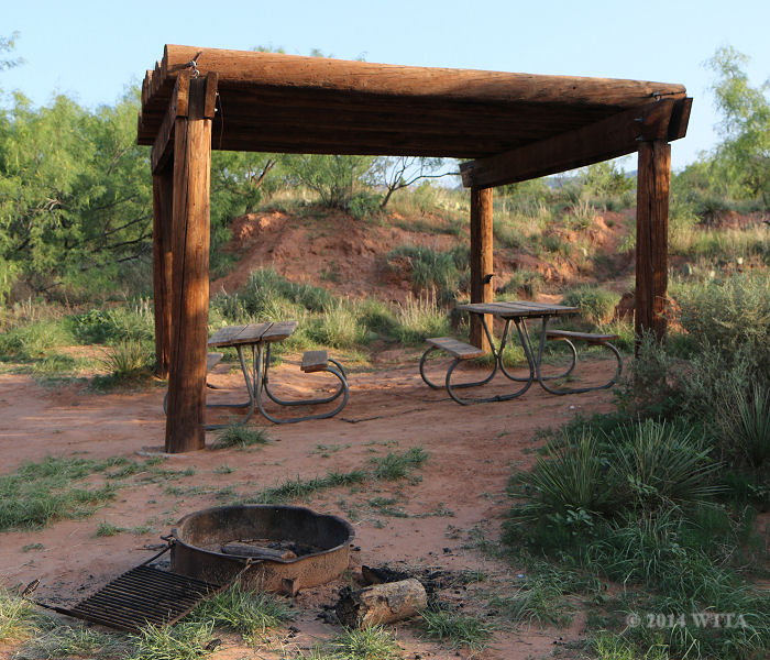 This Picnic area with two picnic tables, a wooden awning, and a fire ring is at the horse camping area near the pens at Palo Duro Canyon State Park.
