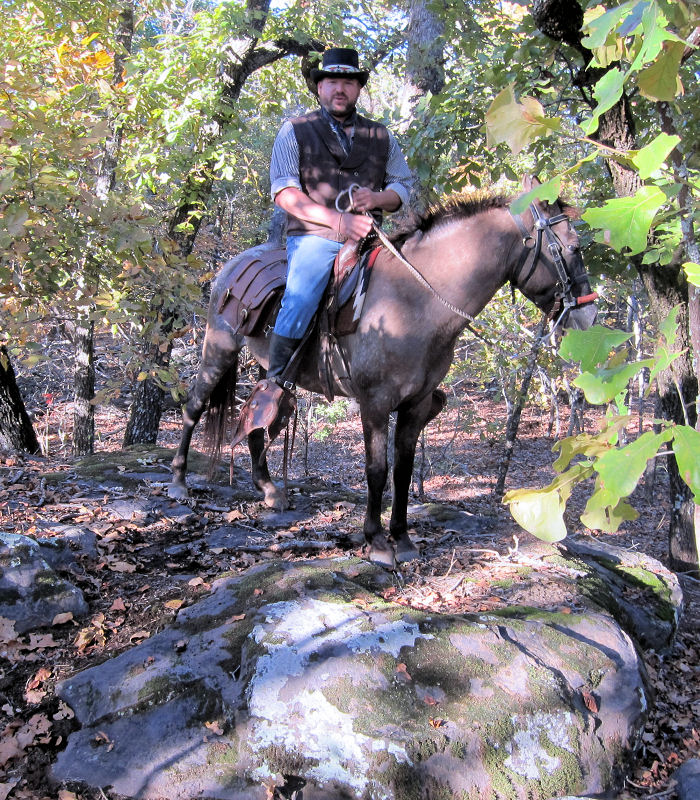 Curtis George riding Dragonfly, shows me rock formations which are hiding in the shadows of the forest just off the trail.